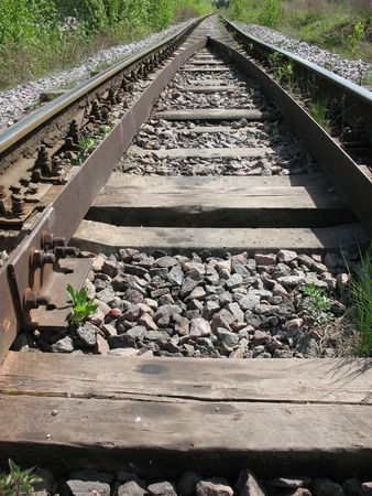 macadam: A running away railroad. A permanent way, a macadam, a sleepers and rails. A skylineand a overcast sky.