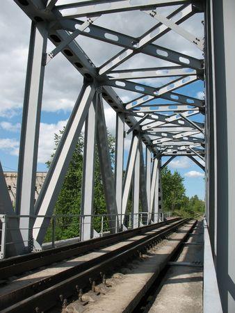 macadam: A running away railroad. A permanent way, a macadam, a sleepers and rails. A skylineand a overcast sky.railway bridge