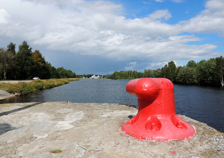 Mooring bollard on the quay against the background of the lock number three of White Sea-Baltic Canal Stock Photo