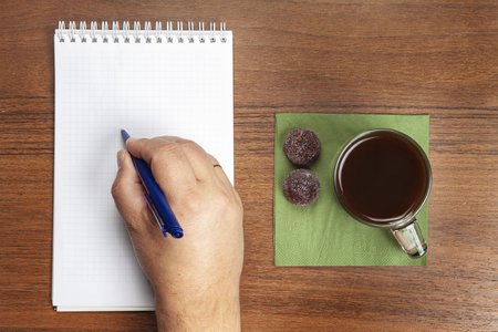The hand is writing with a pen in a notebook, next is a mug with coffee.