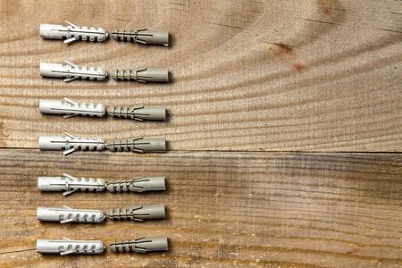 Les chevilles en plastique se trouvent dans une rangée sur un fond en bois.
