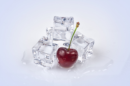 Cherry berry on the background of ice cubes. All on a white background