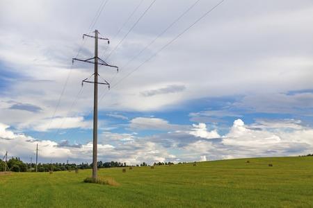 Auf dem Feld steht ein Mast mit Hochspannungsdrähten vor dem Hintergrund des Waldes und des Himmels Standard-Bild