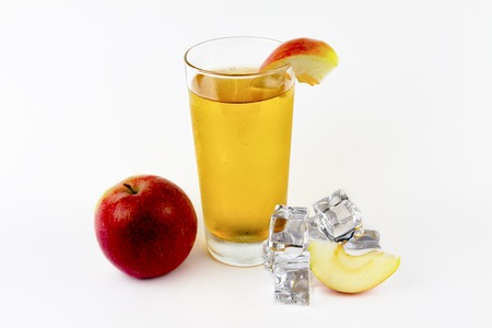 Apple juice in a glass, an apple with ice cubes on a white background.