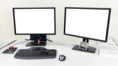 Na stole w biurze stoją dwa monitory komputerowe. Na monitorach biały ekran do wstawiania obrazów lub tekstu.
