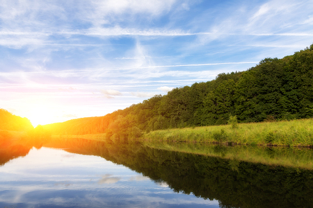 A small river in the summer evening on the shore of a small forest Stockfoto