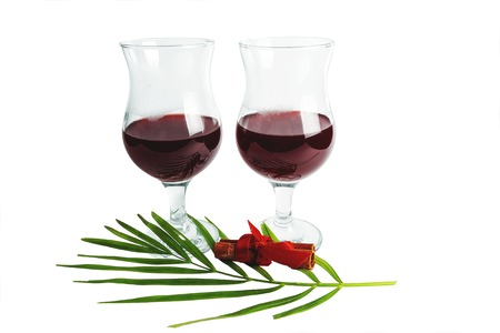 Two glasses with red wine and cinnamon on a white background.