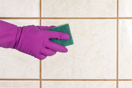 A gloved hand holds a sponge and washes ceramic tiles.