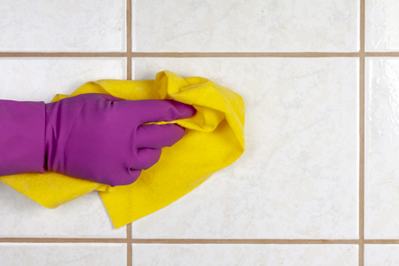 A gloved hand holds a rag and washes ceramic tiles. Stock Photo
