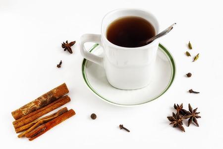Mug with tea teaspoon saucer cinnamon cloves on white isolate background. Reklamní fotografie
