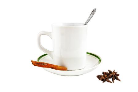 Mug saucer spoon Badian cinnamon on a white background, isolate.