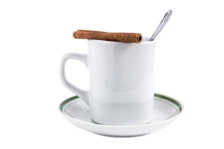 Mug of tea, saucer, spoon, cinnamon on a white background close-up