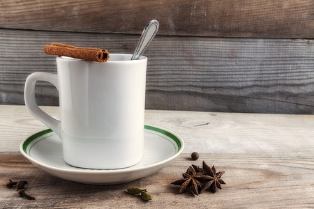 Mug with cloves cinnamon saucer teaspoon tea on a natural wooden background. Reklamní fotografie