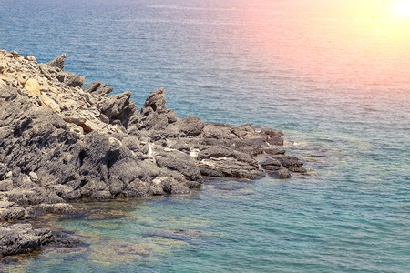 Strongly rocky seashore with sunshine and blue water