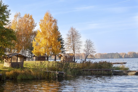 The shore of a large lake with autumn trees and wooden canopies.