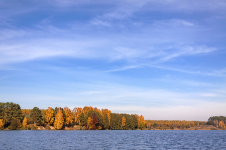 Water with autumn coast and beautiful sky. Фото со стока
