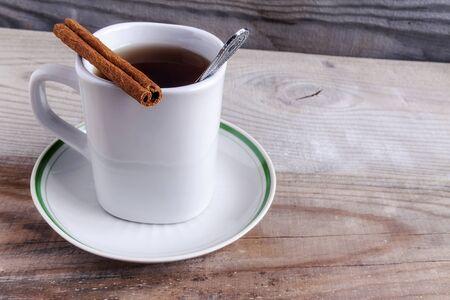 Mug on saucer with tea and cinnamon on wooden background.
