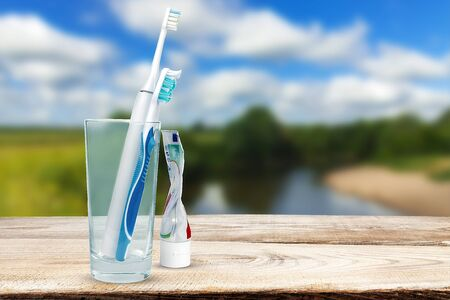 Tooth electrobrush stands in a glass against the background of nature