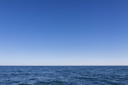 Background, small waves of the sea, and above them the blue sky Zdjęcie Seryjne - 125339848