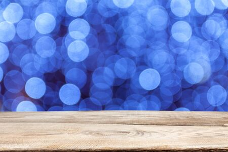 Wooden planks on the background of defocused abstract background of Christmas multi-colored light bulbs