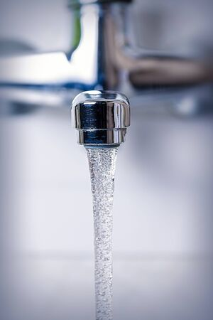 water flows from the kitchen tap, close-up