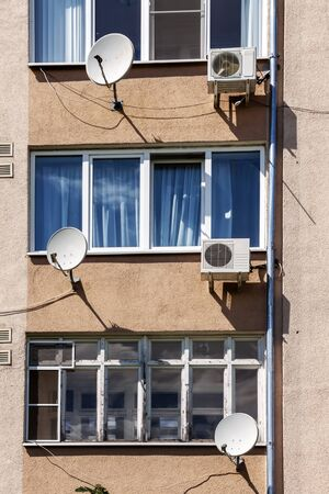 The facade of an apartment building with air conditioning and satellite television antennas