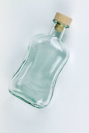 Empty bottle with cork on a light background. 写真素材