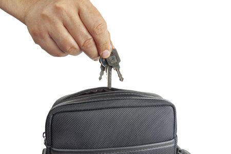 A hand pulls the keys from the bag on a white background, close-up.