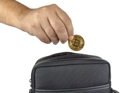 Hand pulls bitcoin from a bag on a white background. Close-up. 写真素材