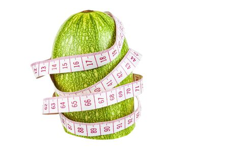 Zucchini with measuring tape on a white background close-up. 写真素材
