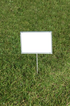 A template of a sign with a white background that stands on a grass lawn.