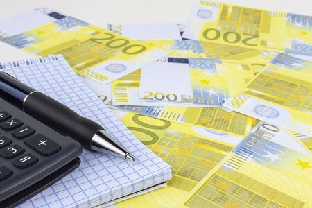 Automatic pen, calculator, notebook on a background of money close-up.