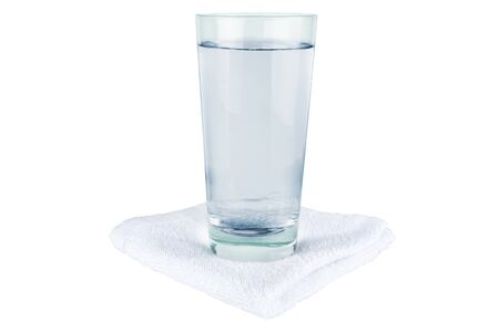 A glass of water stands on a towel