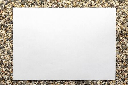 A white sheet of paper lies on a large sea sand