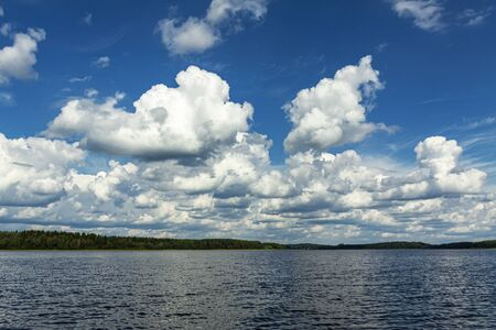 Summer clouds by day over a large lake