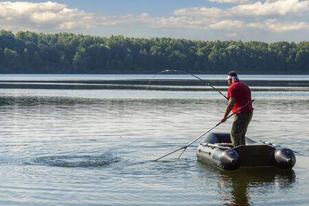 A fisherman on a boat is fishing big fish 写真素材