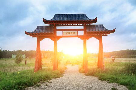 The gates of a Chinese monastery against the backdrop of the rising sun.