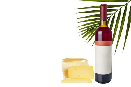 A bottle of wine is standing next to a piece of cheese on a white background. Isolate. Zdjęcie Seryjne