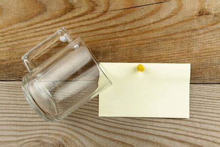 A glass mug hangs on a nail next to a piece of paper for writing text. All on the background of a natural wooden board.