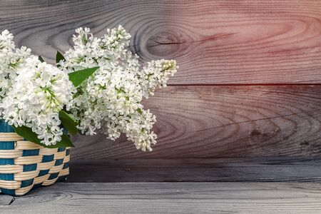 basket with a branch of lilac flower on a wooden background. Zdjęcie Seryjne