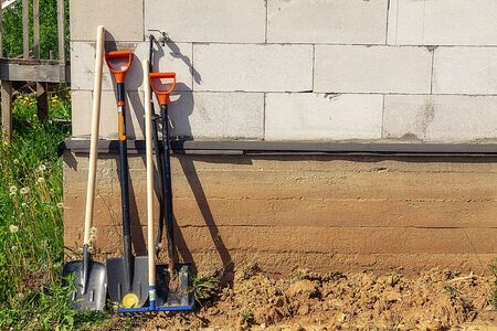 Shovels of different kinds against the background of a brick house