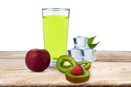 On a wooden board there is a glass with juice next to an apple, kiwi, strawberry, ice cubes, behind a white background