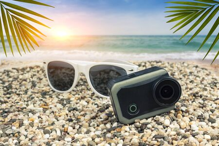 Sun protective goggles with an action camera lie on the beach by the sea