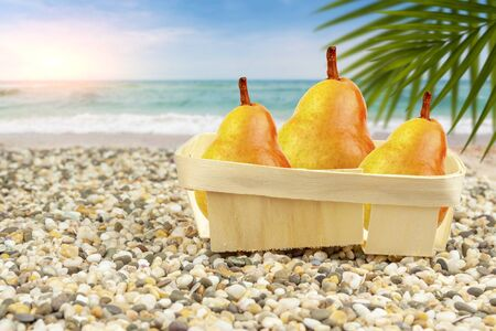 Pears in a basket by the warm sea