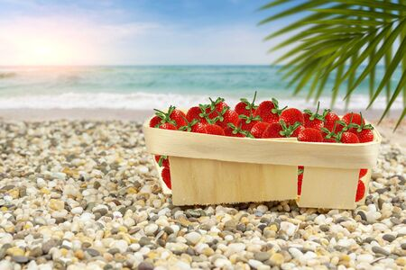 Strawberries in a basket on the shore of the warm sea