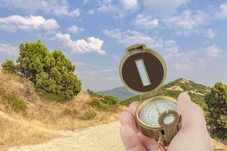 A hand holds a compass on a background of mountains, trees, bushes and sky. Reklamní fotografie