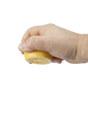 The mans hand squeezes the lemon on a white background.