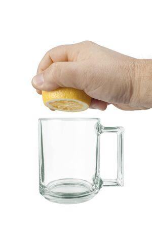 A hand squeezes juice from a lemon into a glass mug Reklamní fotografie