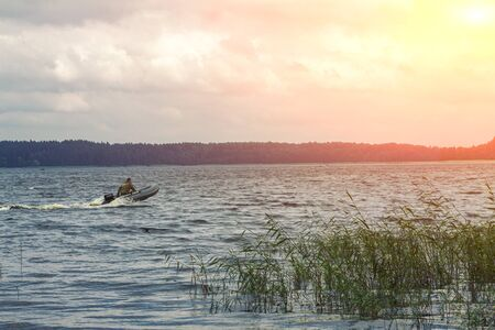 A fisherman on a boat is in a hurry for evening fishing Reklamní fotografie