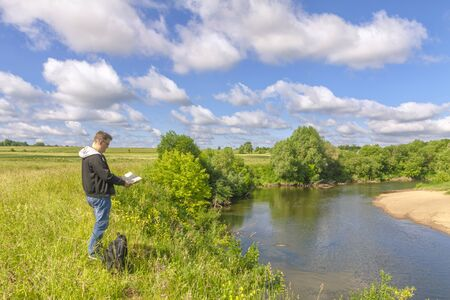 A man stands on the river bank and looks at the map